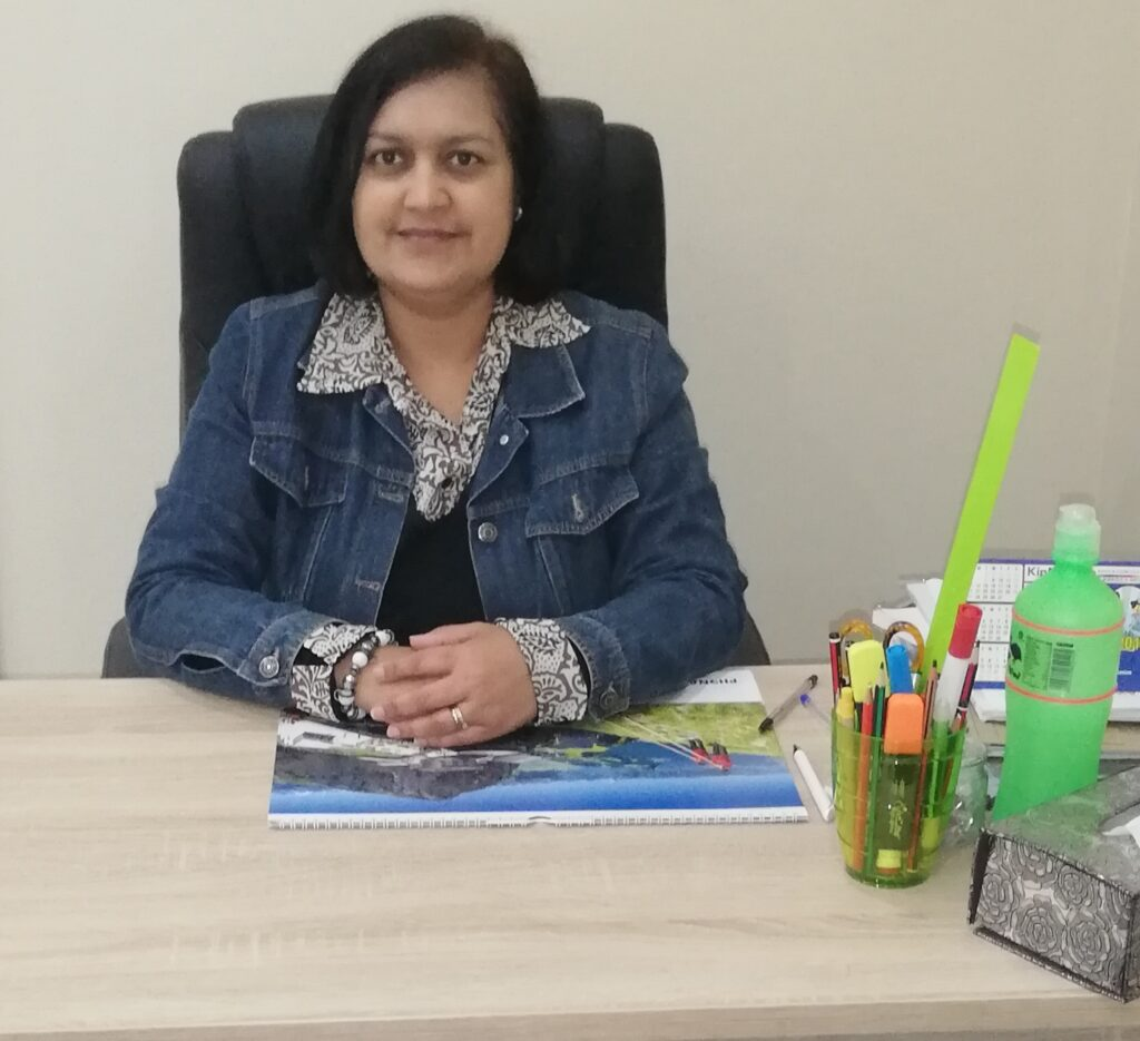 Nishara sitting at her desk in the office