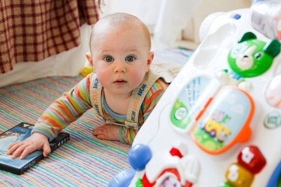 Toddler playing toys. Early stimulation enhances speech in later years.